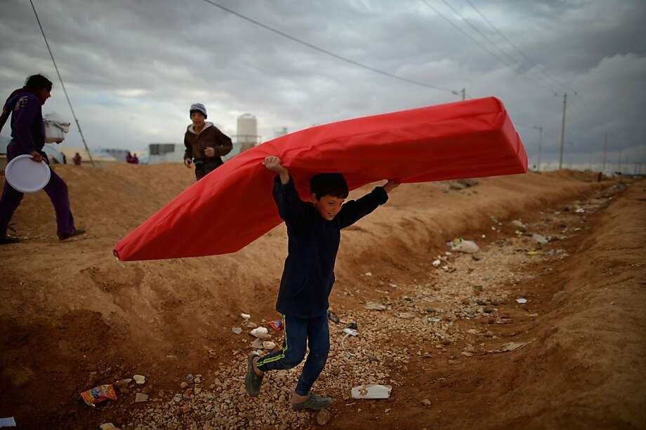 Refugee camp overwhelmed:A boy carries a mattress in the Zaatari refugee camp in Mafrq, Jordan. About 21,000 Syrian refugees have moved into the camp, which was already crowded and struggling with flooding, supply shortages and tent fires, in the past week. Photo: Jeff J Mitchell, Getty Images