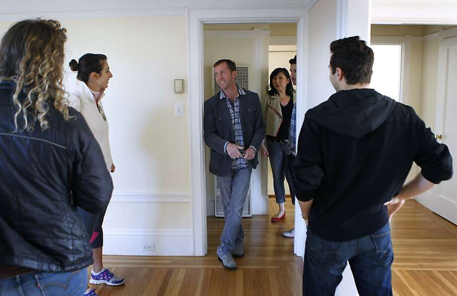 Listing agent Brian Brown (center) shows prospective tenants around a one-bedroom apartment. Photo: Paul Chinn, The Chronicle