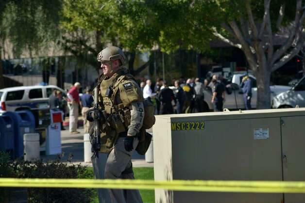 A SWAT police officer leaves the scene after inspecting an office building after a shooting at the buidling in Phoenix on Wednesday, Jan. 30, 2013.  A gunman opened fire at a Phoenix office building on Wednesday, wounding three people, one of them critically, authorities said.  (AP Photo/Patrick Sison) Photo: Patrick Sison, Associated Press / AP