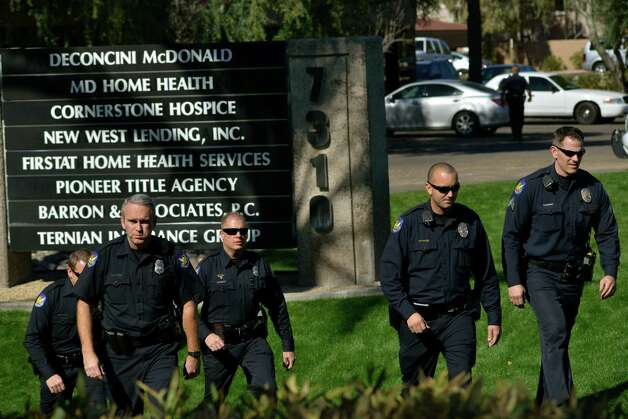 Police officers leave an office building after a shooting at the building in Phoenix on Wednesday, Jan. 30, 2013. A gunman opened fire at the Phoenix office building, wounding three people, one of them critically, authorities said. Police were searching for the shooter. (AP Photo/Patrick Sison) Photo: Patrick Sison, Associated Press / AP