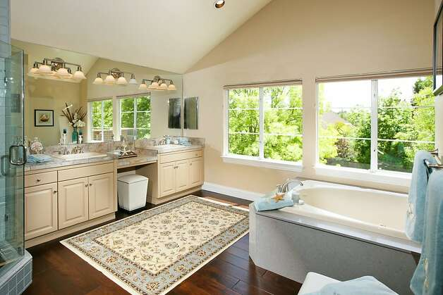 Marble countertops, dual vanities and a jetted tub adorn the master bathroom. Photo: Bob Morris Photography