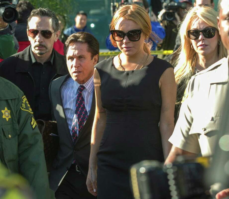 Lindsay Lohan, third from left, her mother Dina Lohan, right, her new attorney Mark Heller, second from left, leave a Los Angeles court, Wednesday, Jan. 30, 2013, in a case filed over the actress' car crash last June. A judge has delayed Lindsay Lohan's trial on three misdemeanor counts. She pleaded not guilty to lying to police, reckless driving and obstructing officers from performing their duties. (AP Photo/Damian Dovarganes) Photo: Damian Dovarganes