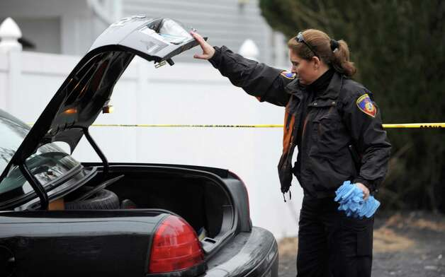 A police officer retrieves a large stack of gloves from a police car as officers work at 172 Vine Road in Stamford on Wednesday, January 30, 2013. Photo: Lindsay Perry / Stamford Advocate