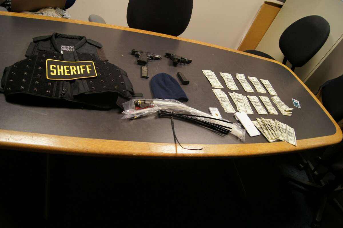Police say a 48-year-old man, now suspected of trying to arrange the murder of someone he thought was a police informant, was originally arrested with these items in his car. Seattle police photo.