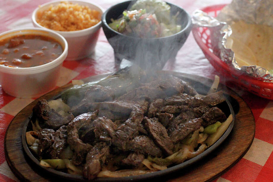 This is the half pound fajitas with grilled onions, rice, beans, pico de gallo, guacamole and tortillas at Pollos Asados Los Nortenos. The restaurant is located at 4642 Rigsby Avenue between W.W. White and Loop 410 on the Southeast Side.  Photo: JOHN DAVENPORT, San Antonio Express-News / ©San Antonio Express-News/Photo Can Be Sold to the Public