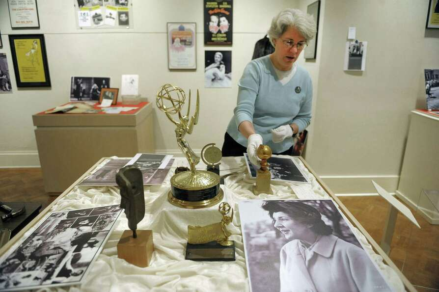 Curator, Stacy Pomeroy Draper shows some of the acting awards of Maureen Stapleton that are on displ
