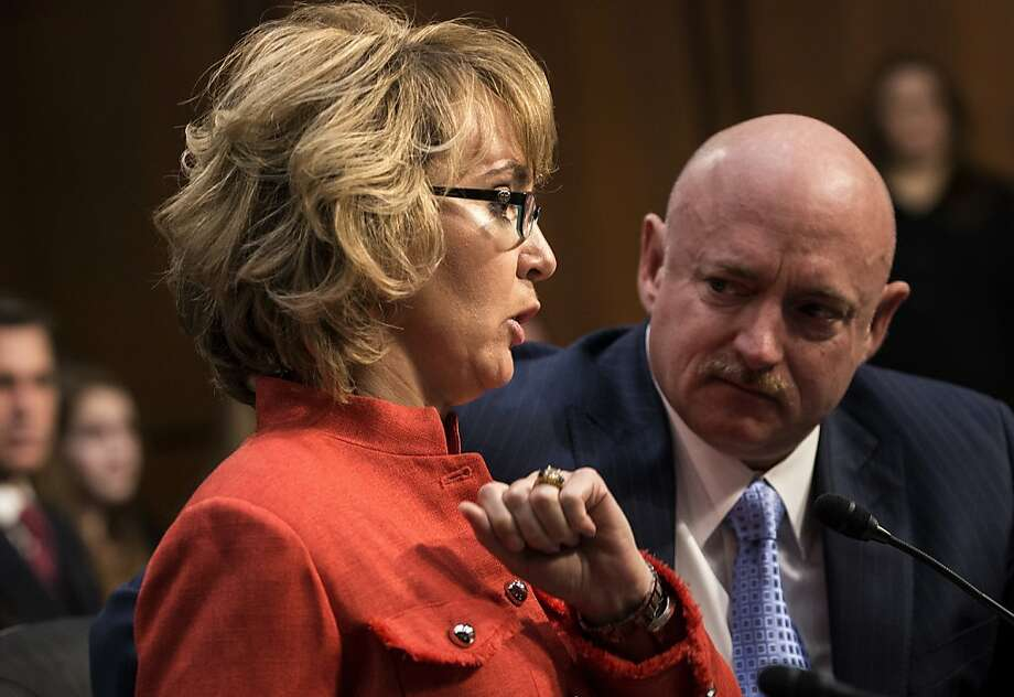 Mark Kelly, husband of former Arizona Rep. Gabrielle Giffords, listens as she makes a statement at a Senate Judiciary Committee hearing on gun violence. Photo: Brendan Smialowski, AFP/Getty Images