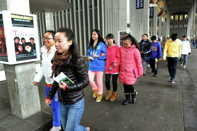 Yu Zou, 24, a PhD student at UAlbany, left, leads a delegation of students and educators from Tianjin, China on a tour of the campus on Wednesday, Jan. 30, 2013, at University at Albany in Albany, N.Y. Tech Valley High School is hosting the delegation as well as the Schoharie, Schodack and Catskill central school districts. Tech Valley High School, Capital Region and Questar IIII BOCES has a sister-school agreement with Tianjin High School No. 41. (Cindy Schultz / Times Union) Photo: Cindy Schultz / 00020972A