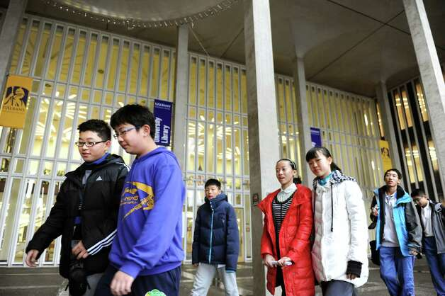 Chen Yu, 12, left, and Li Kuoyuan, 12, second from left, are part of a delegation of students and educators from Tianjin, China on a tour of the campus on Wednesday, Jan. 30, 2013, at University at Albany in Albany, N.Y. Tech Valley High School is hosting the delegation as well as the Schoharie, Schodack and Catskill central school districts. Tech Valley High School, Capital Region and Questar IIII BOCES has a sister-school agreement with Tianjin High School No. 41. (Cindy Schultz / Times Union) Photo: Cindy Schultz / 00020972A