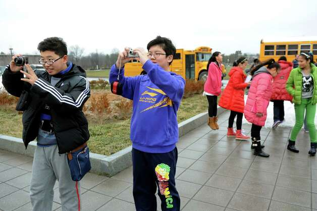 Chen Yu, 12, left, and Li Kuoyuan, 12, center, who are part of a delegation of students and educators from Tianjin, China, take pictures during on a tour on Wednesday, Jan. 30, 2013, at University at Albany in Albany, N.Y. Tech Valley High School is hosting the delegation as well as the Schoharie, Schodack and Catskill central school districts. Tech Valley High School, Capital Region and Questar IIII BOCES has a sister-school agreement with Tianjin High School No. 41. (Cindy Schultz / Times Union) Photo: Cindy Schultz / 00020972A