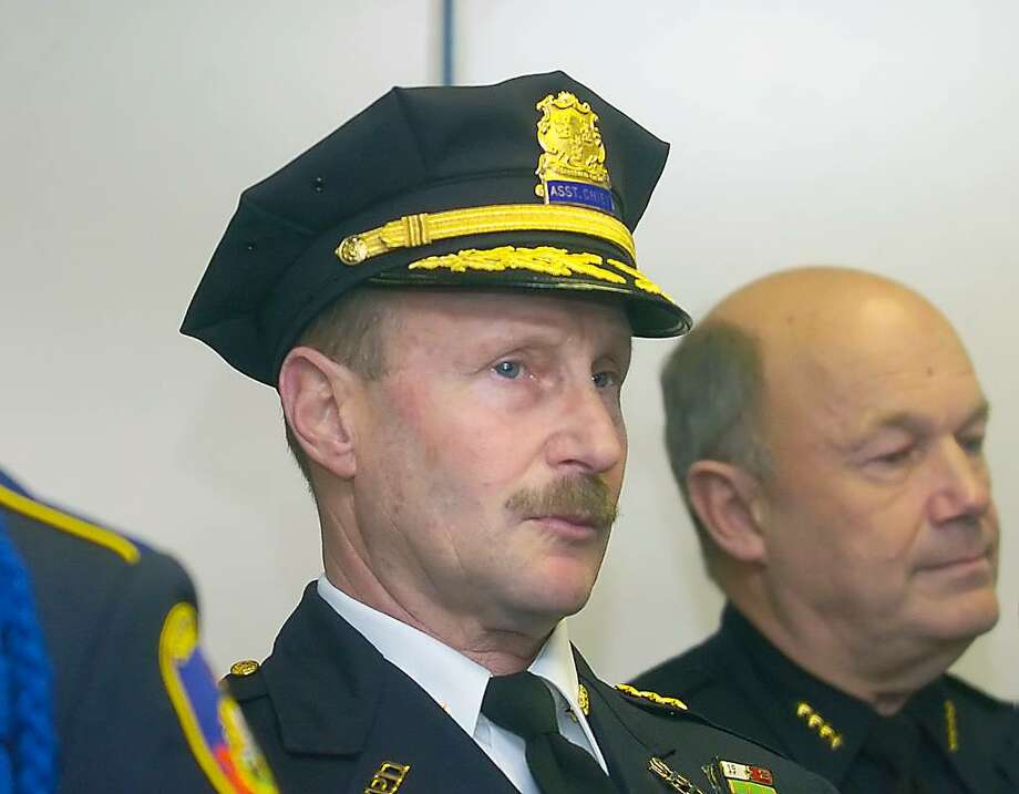 At the promotion ceremony of Stamford Police Department Asst. Chief Robert Nivakoff, center, the 33-year veteran is flanked by Ofc. Chris Brown, left, of the Honor Guard, and Police Chief Brent Larrabee. Andrew Sullivan/Staff photo Photo: Andrew Sullivan / Stamford Advocate