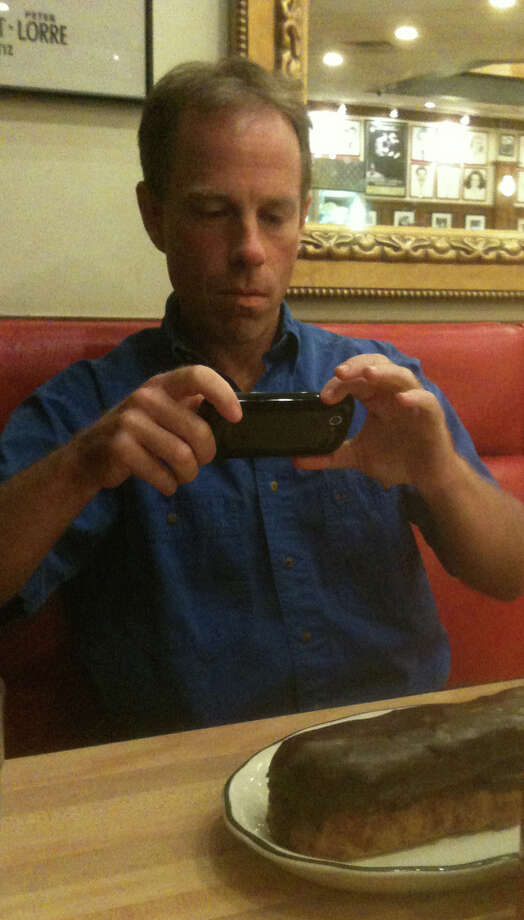 Radio talk-show host Charlie Pallilo takes a photo of his giant chocolate éclair at Kenny & Ziggy's. Photo: Ken Hoffman