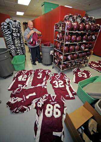 The Central football team turned in their equipment and Offensive Coordinator Coach Tony Cox had the duty of inventorying it all as he looks through bins for all the jerserys.  Dave Ryan/The Enterprise Photo: Dave Ryan