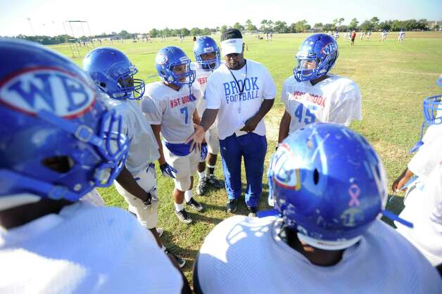 Kirby Jones, linebacker coach with the West Brook High School football team, center, instructs his players before going live on plays during practice on Wednesday. West Brook is getting ready for its first district game. The Bruins open up District 21-5A play on the road against Baytown Sterling. After 5 games, West Brook is 4-1 but head coach Craig Stump says the team needs to improve its run defense. Wednesday,  October 5, 2011.  Valentino Mauricio/The Enterprise Photo: Valentino Mauricio