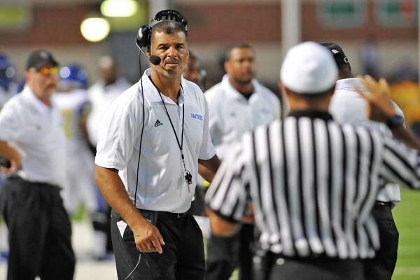 """Assistant Head Coach Ray Metoyer, center,  listens to a ref's call as he explains it on the side line. Ozen High School met West Brook High School in the football season opener Friday August 31, 2012 at the Carrol A """"Butch"""" Thomas Educational Support Center.  Dave Ryan/The Enterprise"""