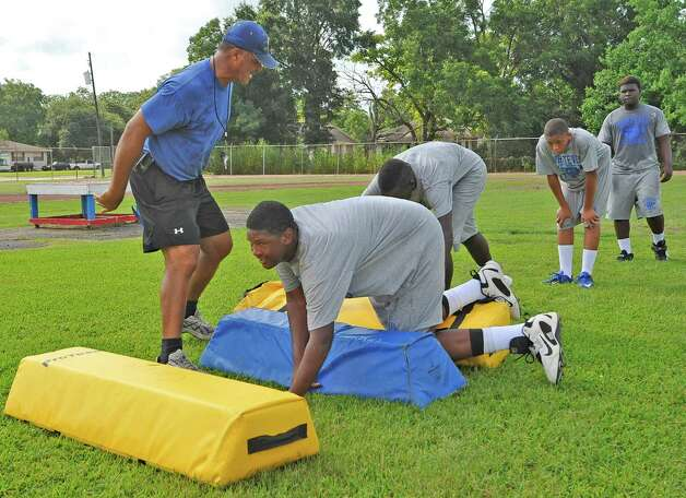 Defensive Line Line Coach Ray Metoyer, left, yells instructions to his players.  The Ozen High School football team opened practice on Monday, August 13, 2012.    Dave Ryan/The Enterprise Photo: Paul Chinn
