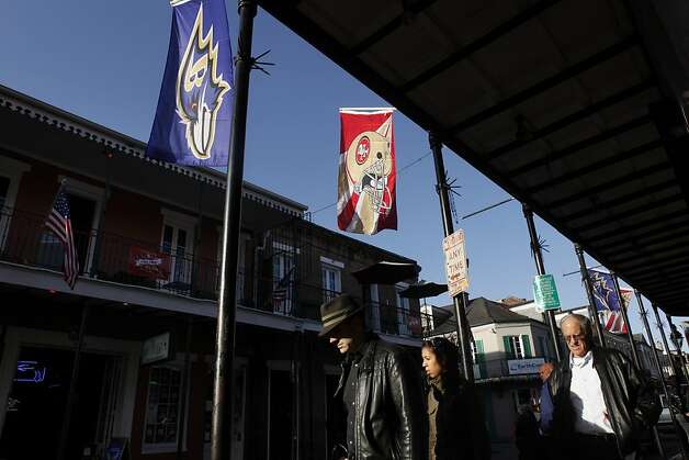 Pedestrians in New Orleans walk on a Bourbon Street festooned with banners for both Super Bowl teams, the Baltimore Ravens and the San Francisco 49ers. Photo: Carlos Avila Gonzalez, The Chronicle