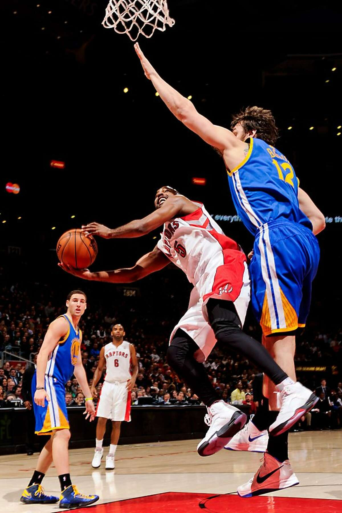 TORONTO, CANADA - JANUARY 28: John Lucas #5 of the Toronto Raptors attempts a shot against Andrew Bogut #12 of the Golden State Warriors on January 28, 2013 at the Air Canada Centre in Toronto, Ontario, Canada. NOTE TO USER: User expressly acknowledges and agrees that, by downloading and or using this photograph, user is consenting to the terms and conditions of the Getty Images License Agreement. Mandatory Copyright Notice: Copyright 2013 NBAE (Photo by Ron Turenne/NBAE via Getty Images)