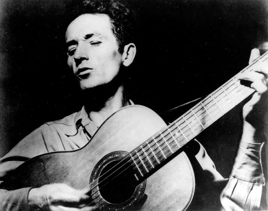 "FILE - This undated file photo shows folk singer Woody Guthrie playing his guitar and singing. Guthrie's writings, recordings and artwork will land in his native state after an Oklahoma foundation bought the collection, with plans for a display that concentrates on his artistry rather than the populist politics that divided local opinion over the years. Guthrie, known for the anthem, ""This Land is Your Land"" and his songs about the poor and downtrodden, is remembered mostly as a musician, composer and singer, but was also a literary figure and an artist, said Bob Blackburn, executive director of the Oklahoma Historical Society.   (AP Photo/File) Photo: STF / ap"