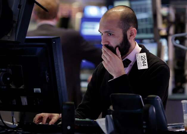 Specialist Fabian Caceres works on the floor of the New York Stock Exchange Wednesday, Jan. 30, 2013.  Stocks are falling after the government revealed that economic growth shrank in the final quarter of 2012, the first time that's happened in more than three years. (AP Photo/Richard Drew) Photo: Richard Drew