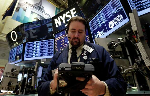 Trader Michael Mozian works on the floor of the New York Stock Exchange Wednesday, Jan. 30, 2013.  Stocks are falling after the government revealed that economic growth shrank in the final quarter of 2012, the first time that's happened in more than three years. (AP Photo/Richard Drew) Photo: Richard Drew