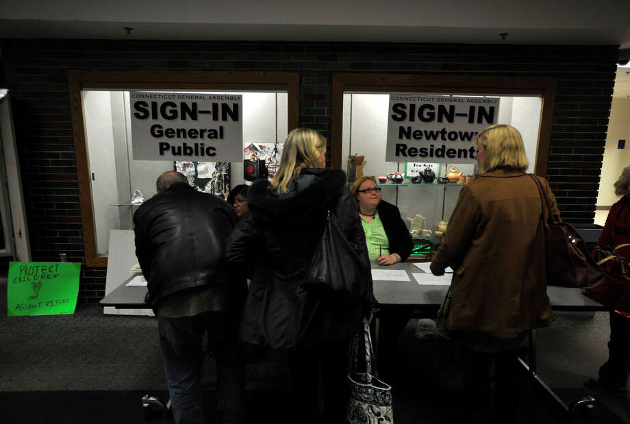 People sign in before Connecticut's Bipartisan Task Force on Gun Violence Prevention and Children's Safety at Newtown High School on Wednesday, Jan. 30, 2013. The task force was created in response to the shooting at Sandy Hook Elementary School. Photo: Jason Rearick / The News-Times