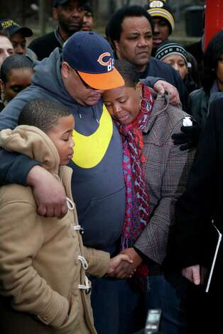 Nathaniel Pendelton, center, hugs his son Nathaniel Jr. and his wife Cleopatra during a news conference with Chicago Police Superintendent Garry McCarthy seeking help from the public in solving the murder of Pendelton's daughter Hadiya Wednesday, Jan. 30, 2013, in Chicago.  Hadiya, 15, who had performed in President Barack Obama's inauguration festivities, was killed in a Chicago park as she talked with friends by a gunman who apparently was not even aiming at her. The city's 42nd slaying is part of Chicago's bloodiest January in more than a decade, following on the heels of 2012, which ended with more than 500 homicides for the first time since 2008. It also comes at a time when Obama, spurred by the Connecticut elementary school massacre in December, is actively pushing for tougher gun laws. (AP Photo/Charles Rex Arbogast) Photo: Charles Rex Arbogast