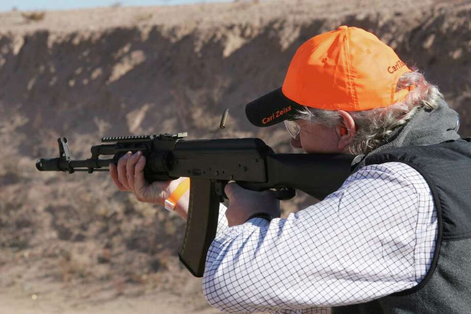 A man tries out the Slide Fire system at the SHOT Show in 2012. The flexible bridge between stock and mainframe works to keep it firing round after round. Photo: Charlie Jacoby / FieldsportsChannel.tv