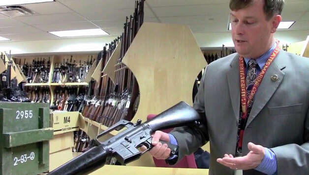 "ATF Agent Max Kingery displays an AR-15 style rifle at the agency's ""gun vault"" in Martinsburg, West Virginia."