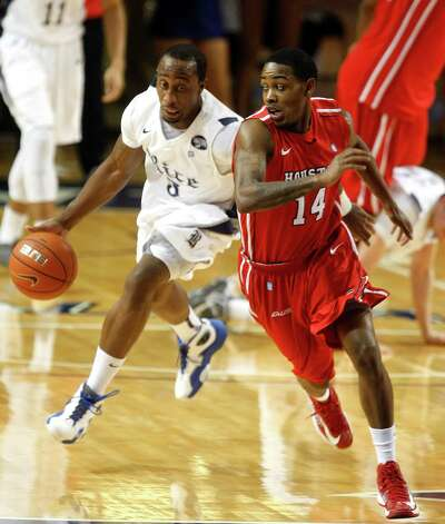 Rice University's Tamir Jackson drives against the University of Houston's Tione Womack. Photo: Johnny Hanson, Houston Chronicle / © 2013  Houston Chronicle