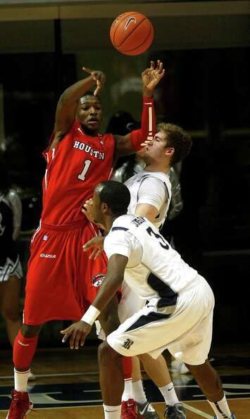 The University of Houston's Mikhail McLean passes the ball past Rice University's Tamir Jackson.
