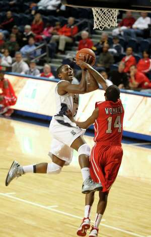 Rice's Keith Washington (5) is fouled by the University of Houston's Tione Womack. Photo: Johnny Hanson, Houston Chronicle / © 2013  Houston Chronicle