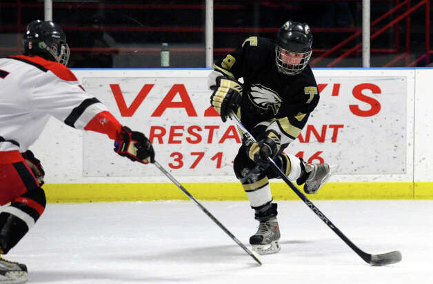 Trumbull's #9 A.J. DiMasi slaps a shot as Fairfield Warde/Ludlowe's #2 Conor Scharlop defends, during boys hockey action at the Wonderland of Ice in Bridgeport, Conn. on Wednesday January 30, 2013. Photo: Christian Abraham / Connecticut Post