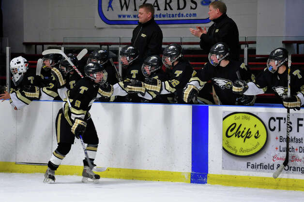Trumbull's #9 A.J. DiMasi celebrates a goal as he passes by his teammates, during boys hockey action against Fairfield Warde/Ludlowe at the Wonderland of Ice in Bridgeport, Conn. on Wednesday January 30, 2013. Photo: Christian Abraham / Connecticut Post