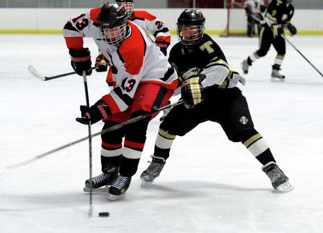 Trumbull's #11 Justin Danforth, right, tries to disrupt a shot by Fairfield Warde/Ludlowe's #13 Charlie Meder, during boys hockey action at the Wonderland of Ice in Bridgeport, Conn. on Wednesday January 30, 2013. Photo: Christian Abraham / Connecticut Post