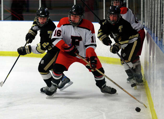 Fairfield Warde/Ludlowe's #16 Mathieu LaRouche moves the puck behind Trumbull's goal, during boys hockey action at the Wonderland of Ice in Bridgeport, Conn. on Wednesday January 30, 2013. Photo: Christian Abraham / Connecticut Post