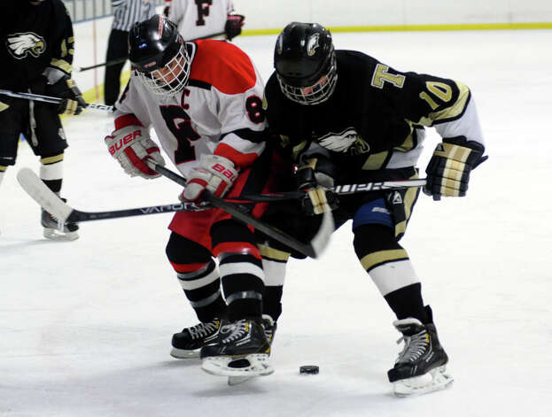Fairfield Warde/Ludlowe's #8 Mike Aquila, left and Trumbull's #10 Alex Pierne try to reach the puck, during boys hockey action at the Wonderland of Ice in Bridgeport, Conn. on Wednesday January 30, 2013. Photo: Christian Abraham / Connecticut Post