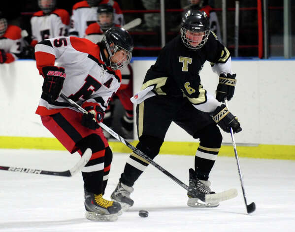 Trumbull's #6 Luke Bolton, right, and Fairfield Warde/Ludlowe's #5 Dan Silvestri go after the puck, during boys hockey action at the Wonderland of Ice in Bridgeport, Conn. on Wednesday January 30, 2013. Photo: Christian Abraham / Connecticut Post