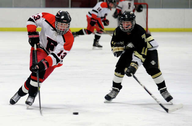 Trumbull's #11 Justin Danforth, right, and Fairfield Warde/Ludlowe's #13 Charlie Meder converge on the puck, during boys hockey action at the Wonderland of Ice in Bridgeport, Conn. on Wednesday January 30, 2013. Photo: Christian Abraham / Connecticut Post