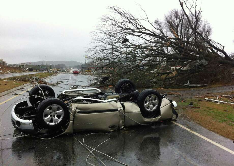 A vehicle lies on a road after a tornado moved through Adairsville, Ga. on Wednesday, Jan. 30, 2013. A fierce storm system that roared across northwest Georgia has left at least one person dead and a trail of damage that included demolished buildings in downtown Adairsville and vehicles overturned on Interstate 75 northwest of Atlanta. (AP Photo/David Goldman) Photo: David Goldman