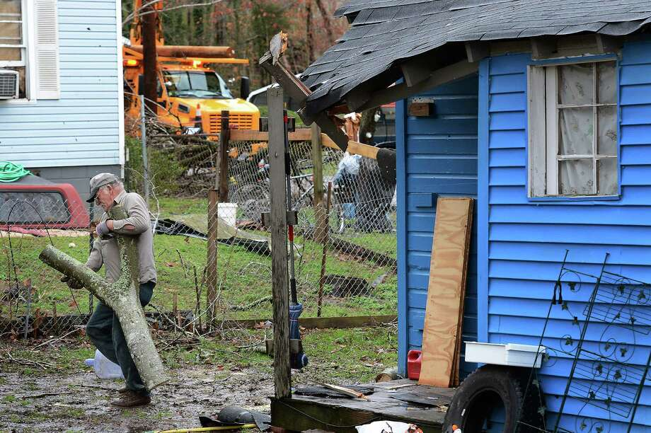 Thomas Ivey carries section of a tree he cut up after it was blown over by tornado that hit the corner of his friend's house     Wednesday, Jan. 30, 2013, in Ashland City, Tenn. Around 25 homes in Ashland City had minor damage. (AP Photo/Mark Zaleski) Photo: Mark Zaleski