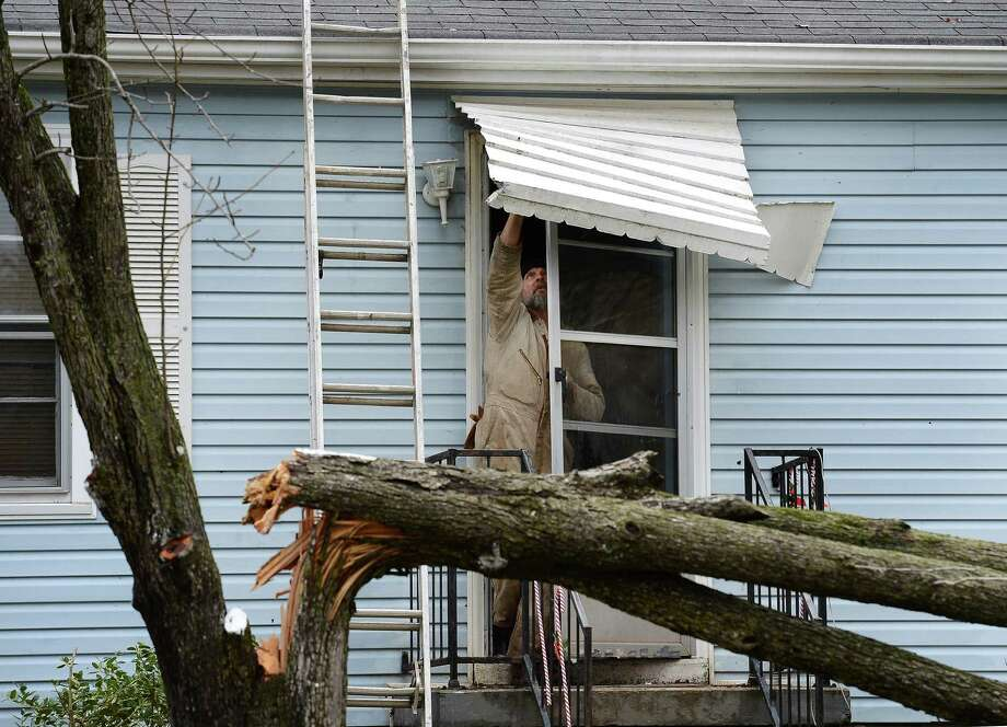 Harold Grant tries to repair his front door awning before cutting up a tree that broke in his front yard  after a tornado touched down, damaging 25 homes and knocking out power Wednesday, Jan. 30, 2013, in Ashland City, Tenn. Around 25 homes in Ashland City had minor damage. (AP Photo/Mark Zaleski) Photo: Mark Zaleski