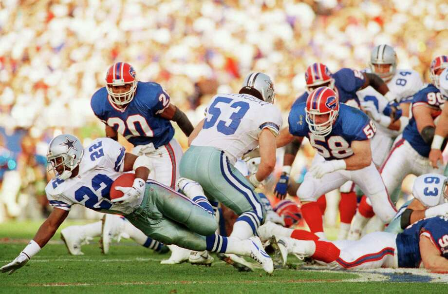 Dallas Cowboys Emmitt Smith (22) stretches for a one-yard loss in the first quarter of Sunday's Super Bowl in Pasadena, Calif., Feb. 1, 1993. Cowboys Mark Stepnoski (53) tries to fend-off Buffalo Bills defenders Henry Jones (20) and Shane Conlan (58) on the play. The Cowboys won 52-17. Photo: Rick Bowmer, Associated Press