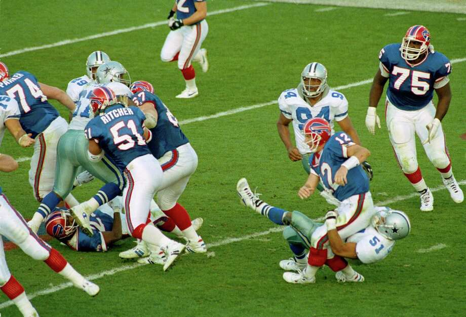 Buffalo Bills' quarterback Jim Kelly (12) buckles on a second quarter hit by Dallas Cowboys' Ken Norton during action in Super Bowl XXVII in Pasadena, Calif., Jan. 31, 1993.  Kelly left the game with an injured knee after the play.  Also seen are Cowboys' Charles Haley (94) and Bills' Howard Ballard (75). Photo: Reed Saxon, Associated Press / 1993 AP