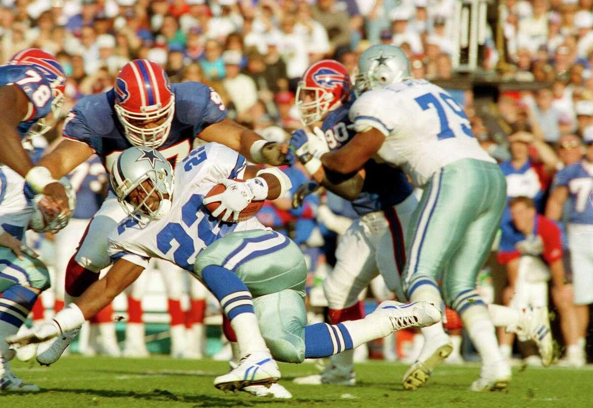 Dallas Cowboys running back Emmitt Smith (22) picks up yardage under Buffalo Bills linebacker Cornelius Bennett during the first quarter of Super Bowl XXVII in Pasadena, Jan. 31, 1993.