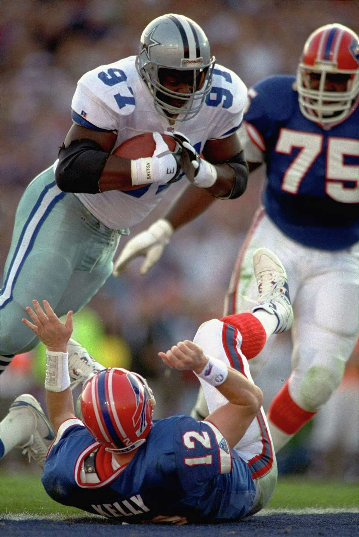 Dallas Cowboys defensive end Jimmie Jones flies over Buffalo Bills quarterback Jim Kelly for a touchdown after recovering Kelly's fumble in the first quarter of Super Bowl XXVII, January 31, 1993.