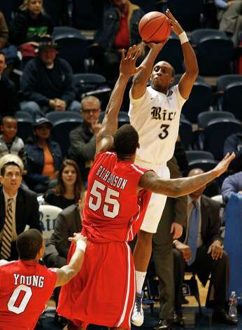 Rice University's Tamir Jackson shoots a three-point basket over the University of Houston's J.J. Richardson. Photo: Johnny Hanson, Houston Chronicle / © 2013  Houston Chronicle