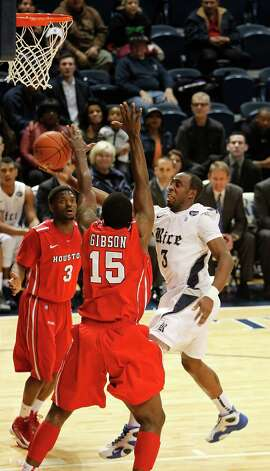 Rice University's Tamir Jackson puts up a shot past the University of Houston's Leon Gibson (15) and J.J. Thompson (3). Photo: Johnny Hanson, Houston Chronicle / © 2013  Houston Chronicle