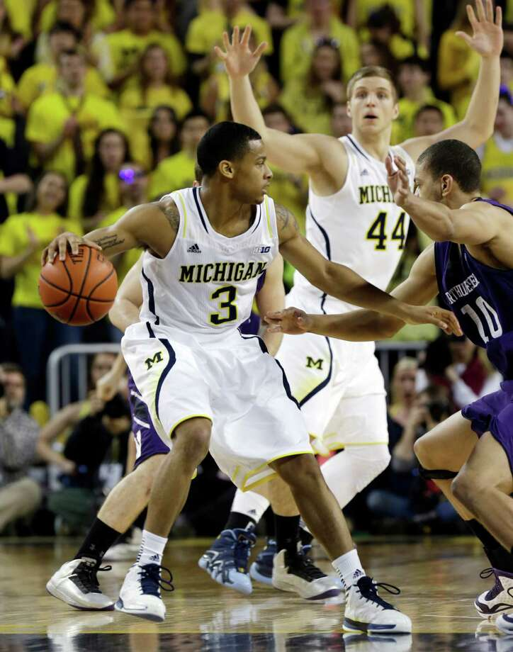 Michigan guard Trey Burke (3) looks to pass around the defense of Northwestern forward Mike Turner (10) during the first half of an NCAA college basketball game in Ann Arbor, Mich., Wednesday, Jan. 30, 2013. (AP Photo/Carlos Osorio) Photo: Carlos Osorio