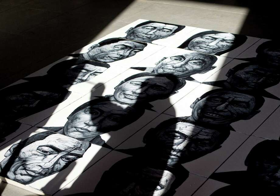 In this Dec. 25, 2012 photo, Beijing-based artist Liu Yi casts his shadow on his painting of portraits of Tibetans who have self-immolated over the past three years as he works at his studio in Songzhuang art village in Tongzhou, on the outskirt of Beijing. Chinese authorities are responding to an intensified wave of Tibetan self-immolation protests against Chinese rule by clamping down even harder — criminalizing the suicides, arresting protesters' friends and even confiscating thousands of satellite TV dishes. (AP Photo/Andy Wong) Photo: Andy Wong, Associated Press / AP